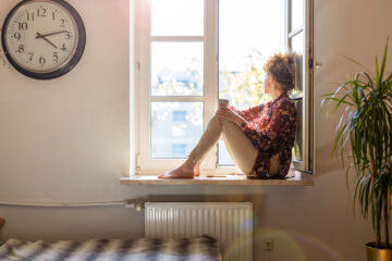 Kvinde alene med en snert af social angst, kigger ud af vinduet